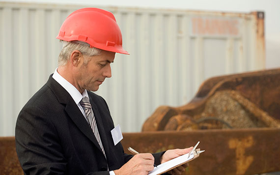 Quality control / quality assurance themed photo - Man in a hard hat with a checklist